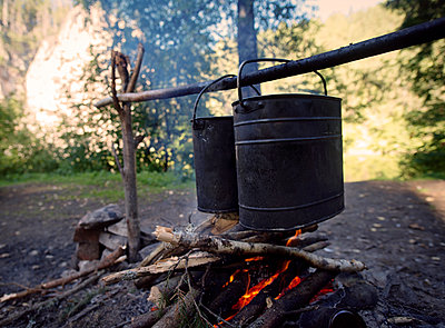 Containers heating over campfire at field - p1166m1099696f by Cavan Images