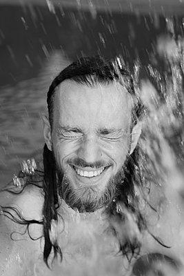 Wasserspritzer im Gesicht eines jungen Mannes - p1519m2124758 von Soany Guigand