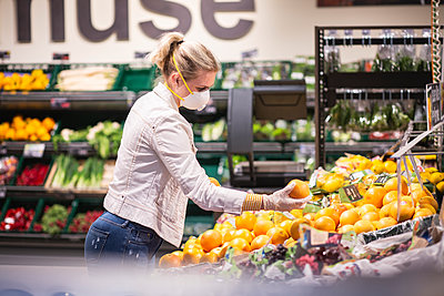 Teenage girl wearing protectice mask and gloves choosing fruits at supermarket - p300m2225034 by Anke Scheibe
