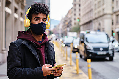 Man wearing jacket and protective face mask using mobile phone while standing on street in city - p300m2250151 by Alvaro Gonzalez