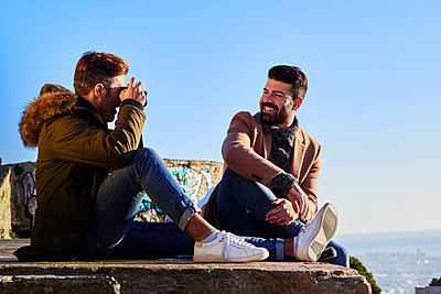 Man looking at boyfriend photographing with camera on viewpoint, Bunkers del Carmel, Barcelona, Spain - p300m2257315 by Veam