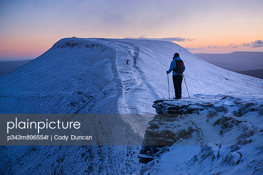 Female hiker looks towards Pen Y Fan at dawn from Corn Du - p343m896554f by Cody Duncan
