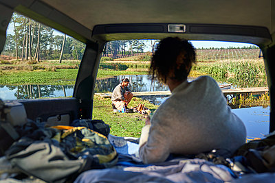 Young woman in car watching boyfriend prepare campfire - p1023m2212957 by Trevor Adeline
