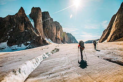 Mounatineers hike around glacial crevasses, Baffin Island - p1166m2189731 by Cavan Images