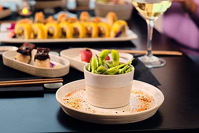 Fresh edamame in bowl at table in restaurant - p300m2264630 by Antonio Ovejero Diaz