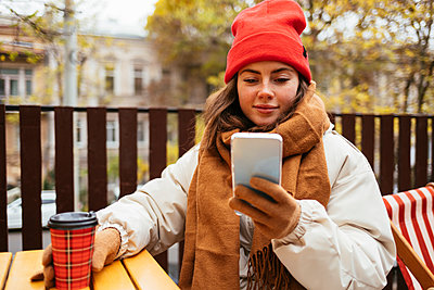 Woman wearing knit hat and scarf using smart phone while sitting at sidewalk cafe - p300m2267176 by alev