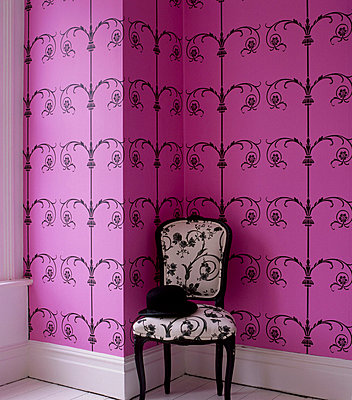 Room with pink patterned wallpaper and upholstered chair - p349m695194 by Emma Lee