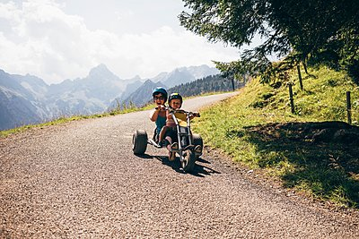 Mother and son wearing helmets riding go cart on curved road, looking at camera mouth open, Bludenz, Vorarlberg, Austria - p429m1105732 by JFCreatives