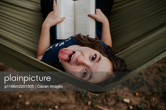 Preteen girl sitting in hammock sticking out her tongue - p1166m2201305 by Cavan Images