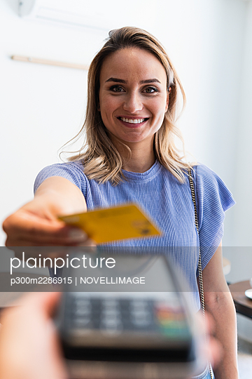 Smiling young woman making payment through credit card at coffee shop - p300m2286915 by NOVELLIMAGE