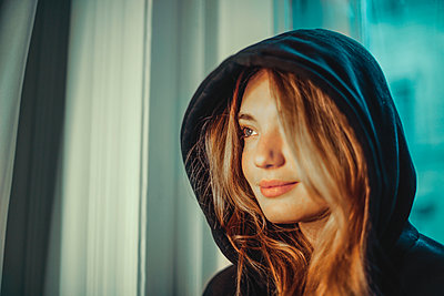 portrait of a beautiful young woman with a hood - p1166m2163035 by Cavan Images