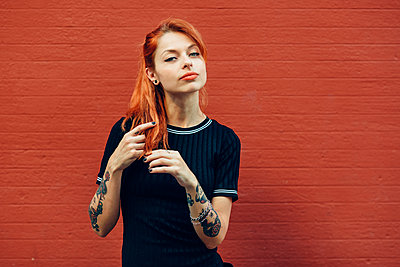Portrait of red-haired tattooed woman standing at a brick wall - p300m2132022 by Javier Sánchez Mingorance