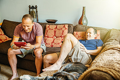 Caucasian gay couple relaxing in living room - p555m1421630 by Inti St Clair photography