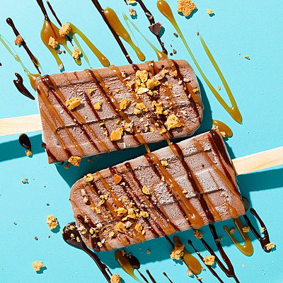 Two homemade fudge iced lollies with sprinkled and drizzled nuts, caramel and chocolate sauce on blue background, overhead view - p924m2138334 by Ryan Benyi Photography