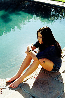 Young woman in deep thought sitting poolside - p967m791693 by Wessel Wessels