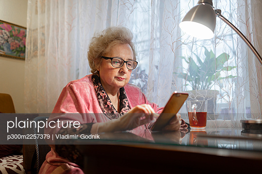 Elderly woman using smart phone under electric lamp on table in living room - p300m2257379 by Vladimir Godnik