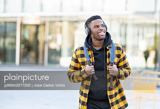 Cheerful man wearing checked yellow jacket listening music through headphones - p300m2277202 by Jose Carlos Ichiro