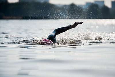 Woman swimmer training in river on summer - p1630m2196912 by Sergey Mironov