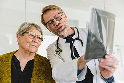 Doctor discussing x-ray image with senior patient - p300m2180994 by Mareen Fischinger