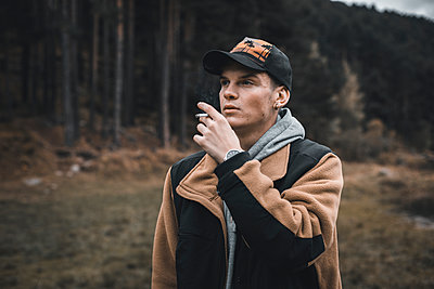 Young man looking away while smoking standing in forest during autumn - p300m2224875 by Aitor Carrera Porté