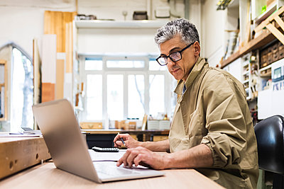 Mature male craftsperson working on laptop at workbench - p300m2293689 by Eugenio Marongiu