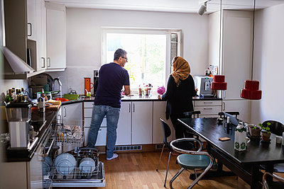 Rear view of couple standing in kitchen - p426m1193030 by Maskot