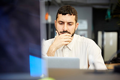 Stressed creative businessman looking at laptop while sitting in office - p426m2074700 by Maskot