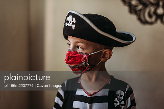 Lifestyle portrait of young boy dressed as pirate with face covering - p1166m2207774 by Cavan Images