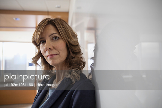 Portrait serious, confident businesswoman at whiteboard in conference room - p1192m1231160 by Hero Images