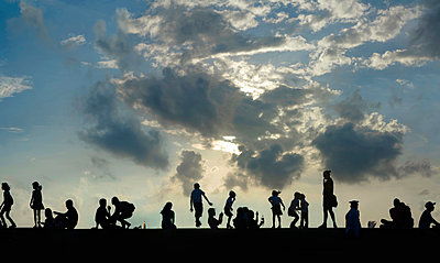 Group of people against sky at sunset, Manila, Philippines - p343m2028849 by Per-Andre Hoffmann