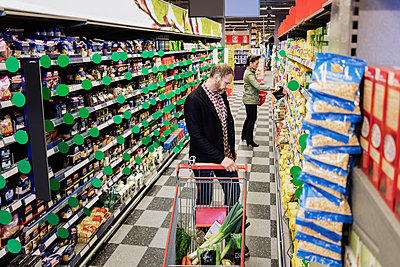 Man and woman shopping in grocery store - p426m1148162 by Maskot