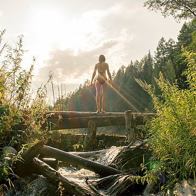 Caucasian woman standing on log over waterfalls - p555m1303607 by Aliyev Alexei Sergeevich