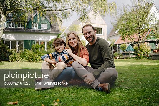 Happy family sitting on grass in their garden - p300m2167325 von Kniel Synnatzschke