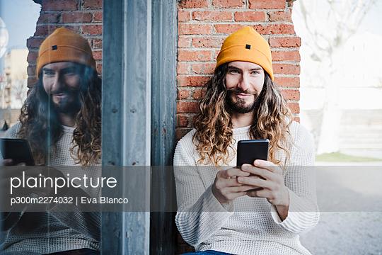 portrait of handsome man sitting by window, Madrid, Spain - p300m2274032 von Eva Blanco