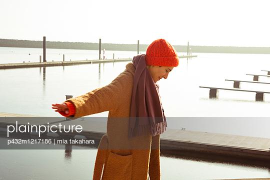 Gut gelaunte junge Frau am Ufer - p432m1217186 von mia takahara