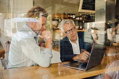 Two businessmen with laptop meeting in a cafe - p300m2140480 by Gustafsson