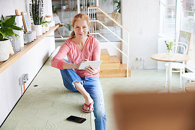 Woman with digital tablet sitting on countertop at home - p300m2266094 by Jo Kirchherr