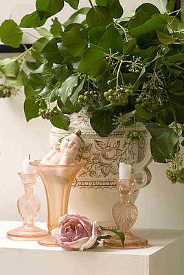 Porcelain vase filled with berried ivy foliage beside pink glass candlesticks - p349m790533 by Polly Eltes