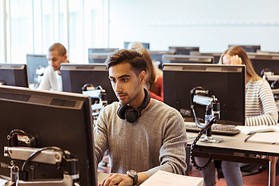 Serious young man using computer at desk with students in background at library - p426m2072217 by Kentaroo Tryman