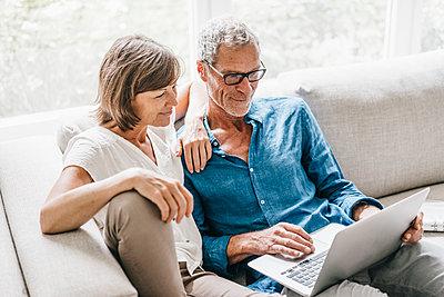Reifes Paar mit Laptop auf dem Sofa - p586m1178497 von Kniel Synnatzschke