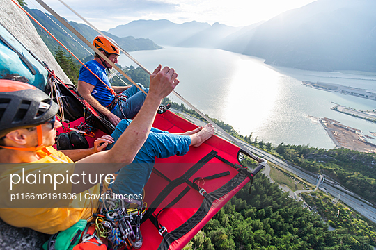 Two men sitting on a portaledge enjoying sunset and view in Squamish - p1166m2191806 by Cavan Images