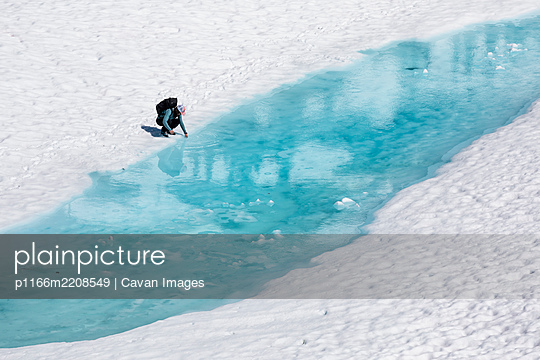 Drone view of unrecognizable female hiker resting and putting hand in melting lake with clear blue water during vacation in British Columbia - p1166m2208549 by Cavan Images