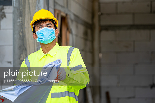 Construction worker wear protective face masks for safety in con - p1166m2236859 by Cavan Images