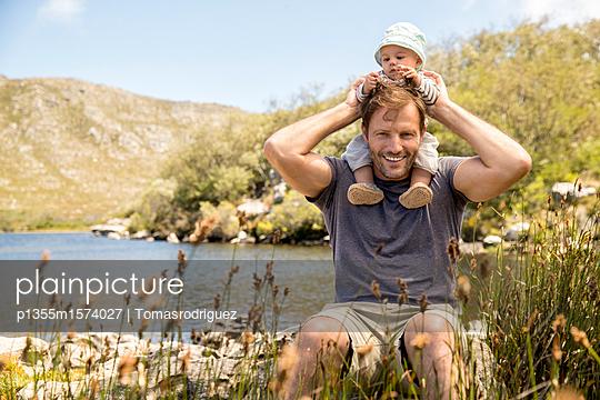 Vater und Baby am Seeufer - p1355m1574027 von Tomasrodriguez