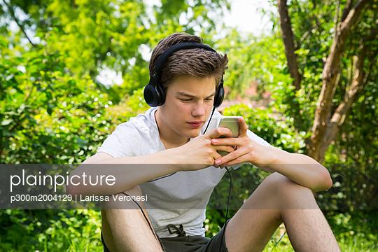 Boy sitting in the garden listening music with headphones and smartphone - p300m2004129 von Larissa Veronesi