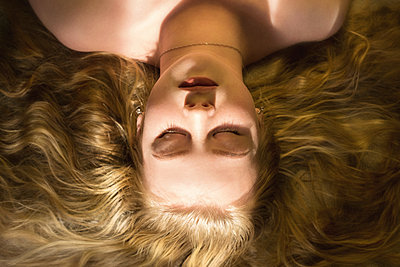 High angle close-up of woman with blond hair sleeping on bed at home - p1166m2025409 by Cavan Images