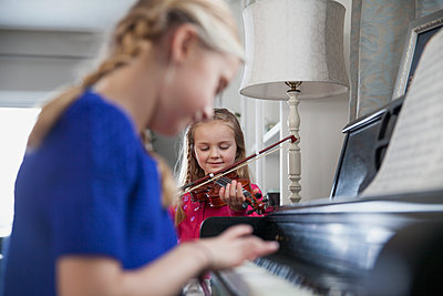 Sisters playing music together - p1192m1219241 by Hero Images