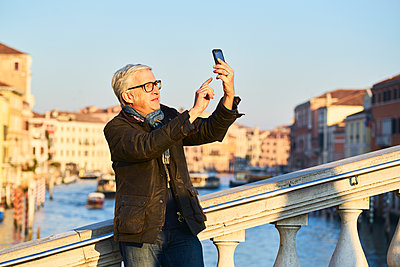 Man is photographing with the smartphone on a bridge in Venice - p1312m2082173 by Axel Killian