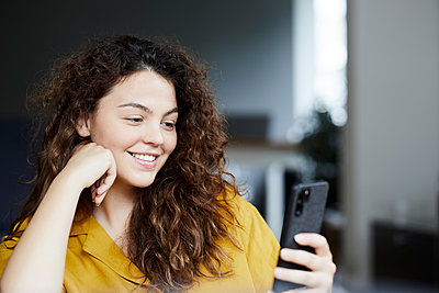 Smiling beautiful woman using smart phone while sitting at home - p300m2206704 by Jo Kirchherr