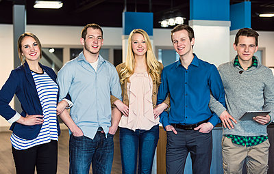 Portrait of a group of young millennial professionals standing together arm in arm in the workplace; Sherwood Park, Alberta, Canada - p442m1580580 by LJM Photo